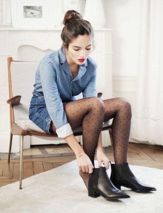 Chica usando camisa y short de mezclilla, con medias negras y botines del mismo color