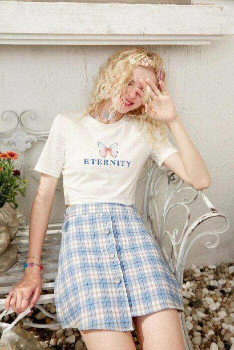 Chica usando una playera blanca con estampado y falda a cuadros de color azul cielo y blanco
