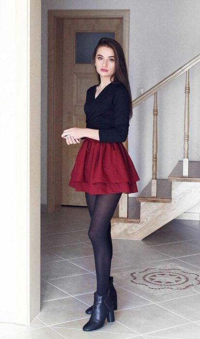 Chica usando blusa negra, falda color guinda, con medias y botas color negro