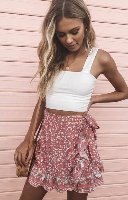 Girl wearing white tank top, with pink skirt with white print and details