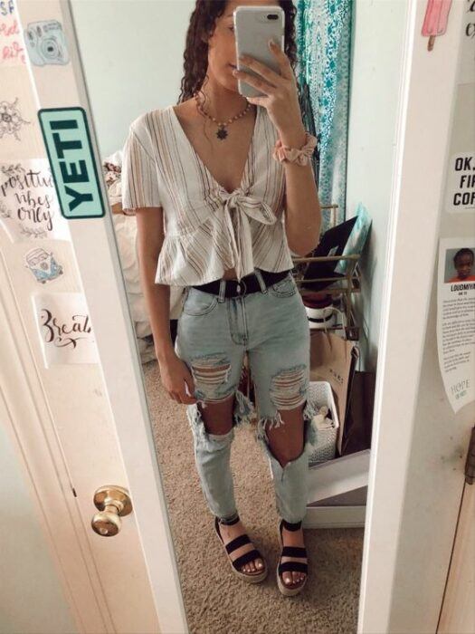 Girl wearing loose-fitting light-colored blouse, with ripped mom jeans and black sandals