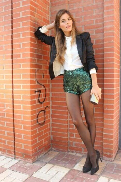 Chica usando camisa color blanco, con saco color negro, short de lentejuelas color verde, con medias y zapatos de tacón color negro