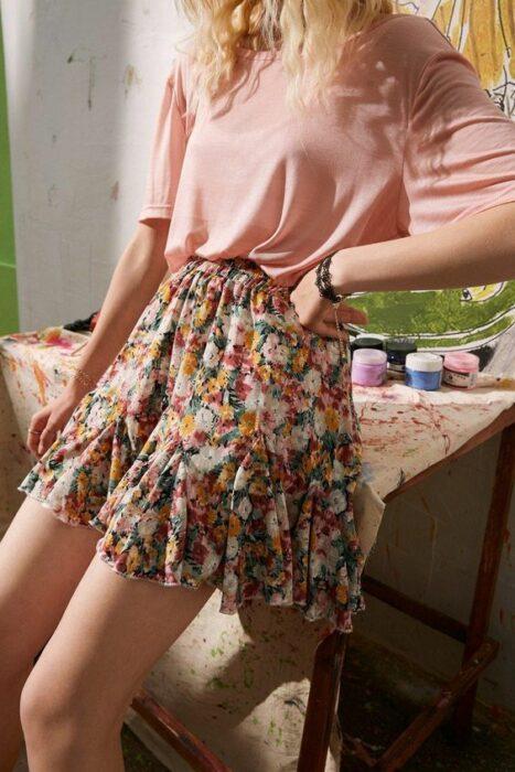 Chica usando blusa rosa de manga corta y falda corta de estampado floreado