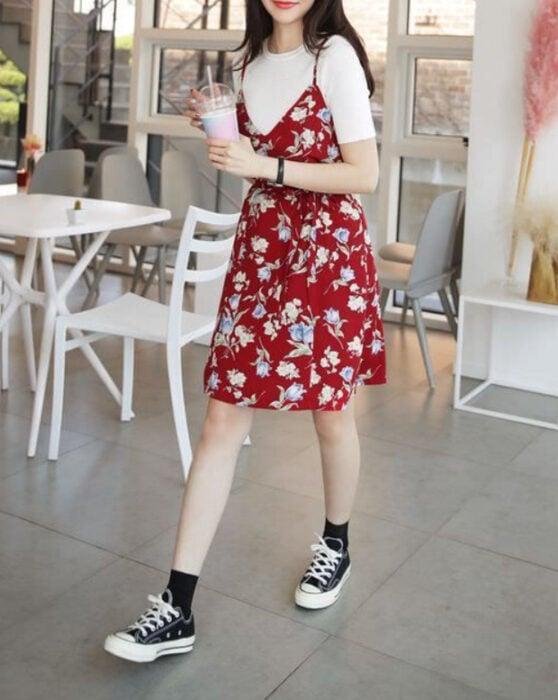 Chica usando un vestido color rojo con estampado de flores en colores claros, con una blusa blanca debajo y converse negros