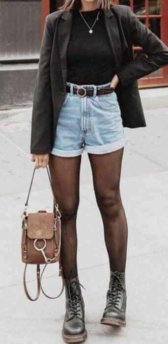 Chica usando blusa y blazer color negro, con short de mezclilla, y medias y zapatos también negros