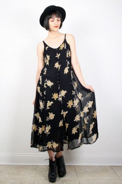 Girl wearing a long black dress with yellow flower print, black ankle boots and a black hat