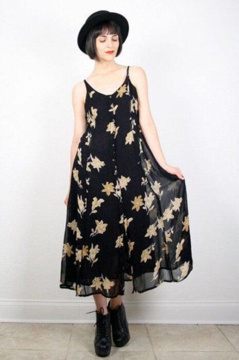 Chica usando un vestido largo de tirantes color negro con estampado de flores amarillas, botines negros y sombrero de color negro