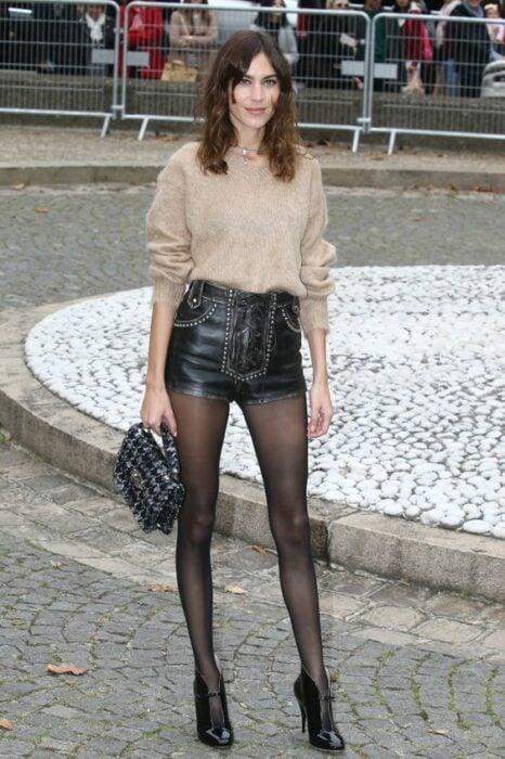 Chica usando suéter beige, con short, medias y botines color negro
