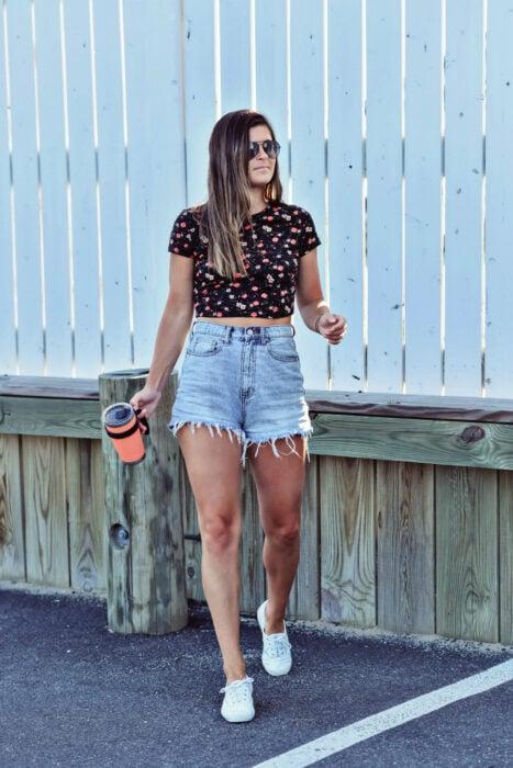 Chica usando unos mom shorts acompañados de blusa y tenis