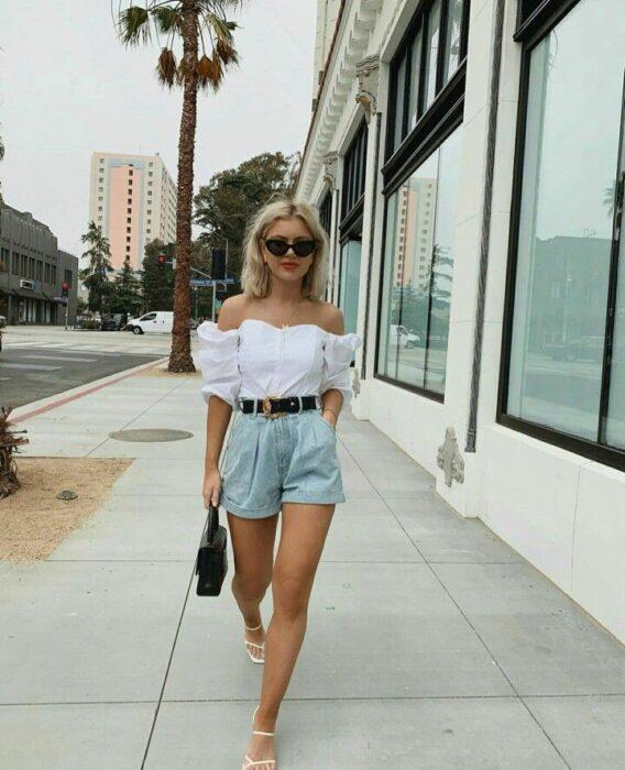 Chica usando unos mom shorts acompañados de blusa hasta los hombros y sandalias