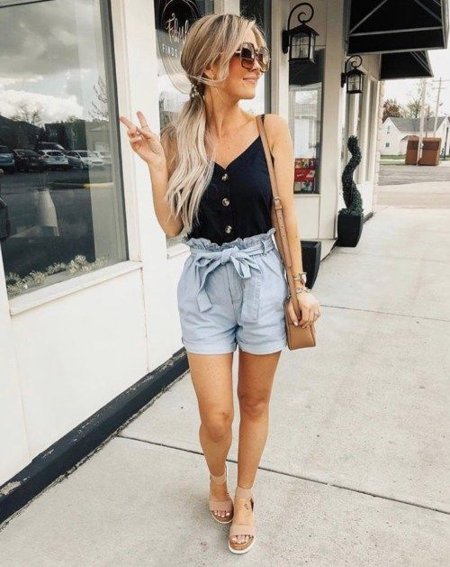 Chica usando unos mom shorts acompañados de un top de color negro