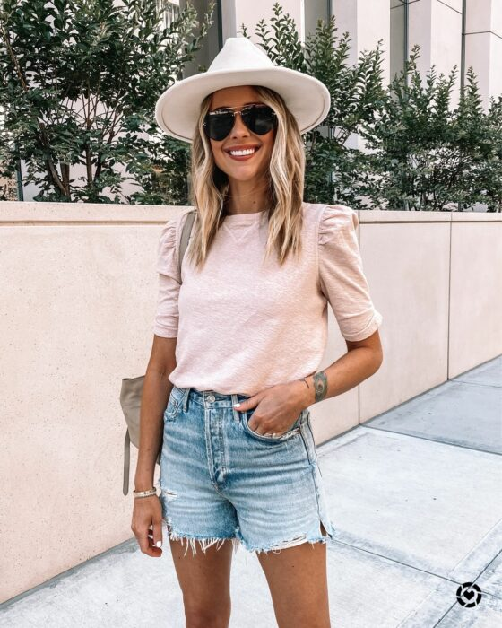 Chica usando unos mom shorts acompañados de blusa rosa y sombrero