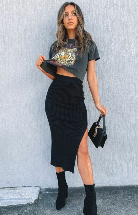 Girl wearing thigh-length slit skirt and lion print t-shirt