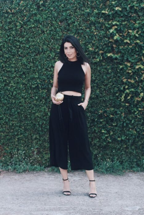 Girl wearing a black top and culottes with sandals