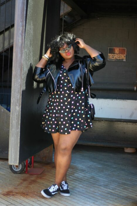 Girl wearing a black dress with colored dots, leather jacket and tennis vans