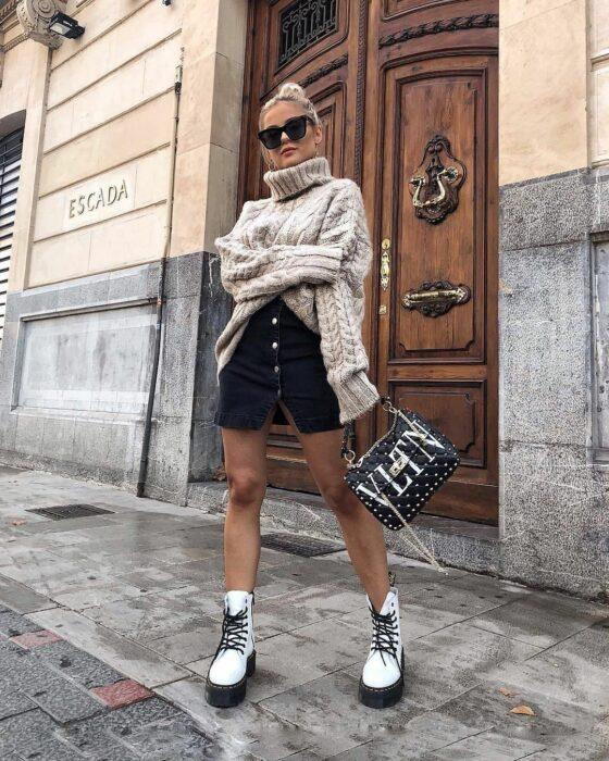 Chica usando una falda negra, suéter oversized y botas blancas Dr. Martens