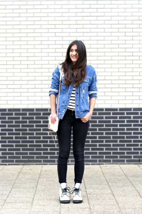 Girl wearing a casual look with black jeans, denim jacket and striped blouse accompanied by Dr. Martens boots
