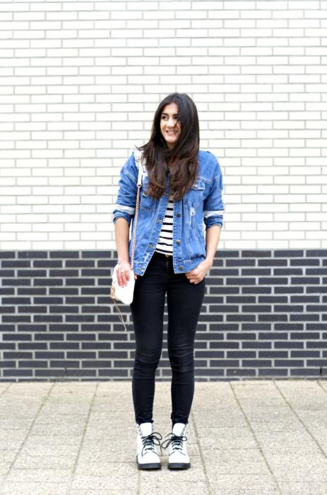 Chica usando un look casual con jeans negros, chaqueta de mezclilla y blusa a rayas acompañada de unas botas Dr. Martens