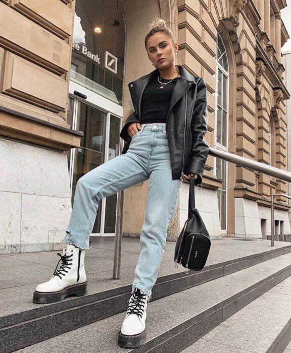 Girl wearing jeans, leather jacket, black blouse and white Dr. Martens boots with black straps