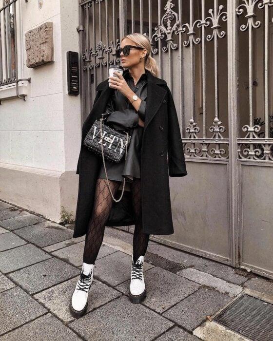 Chica usando un outfit de color negro con botas dr. Martens color blanco mientras se toma un café y posa para una fotografía