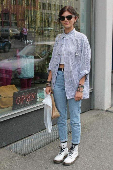 Girl wearing jeans, Dr. Martens boots and a long blue blouse