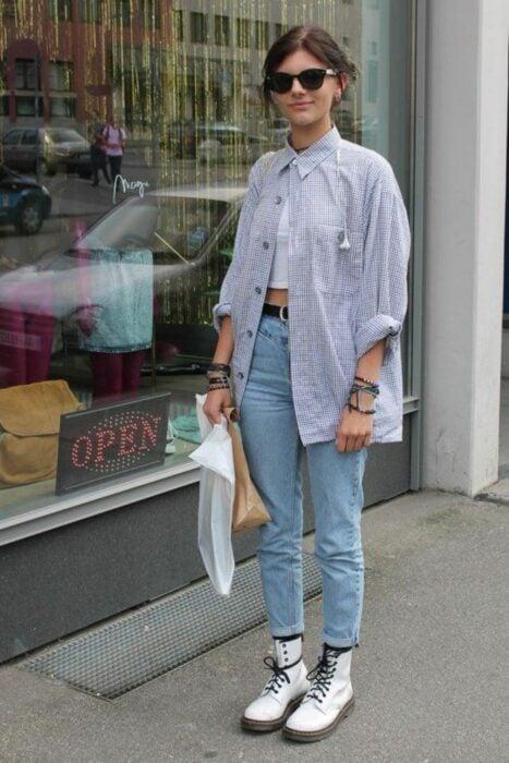 Chica usando jeans, botas Dr. Martens y una blusa larga de color azul