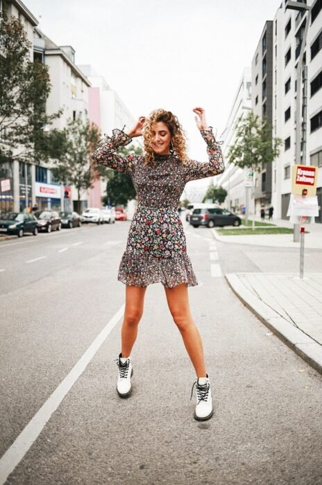 Girl wearing a floral print dress and dr. Martens white while posing in the street for a photograph