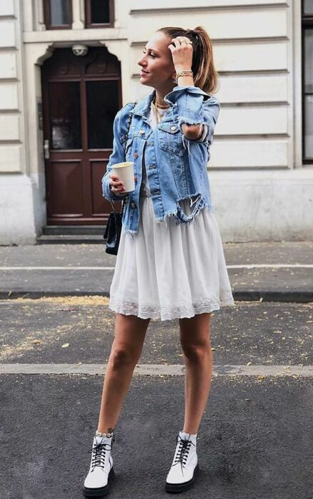 Girl wearing a white dress with white Dr. Martens boots, denim jacket and black handbag while posing for a picture in the middle of the street