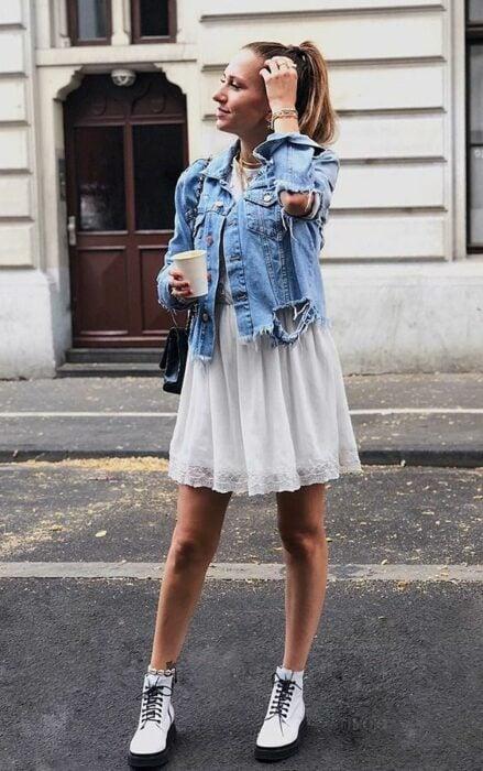 Chica usando un vestido de color blanco con botas Dr. Martens de color blanco, chaqueta de mezclilla y bolso negro mientras posa para una fotografía en medio de la calle