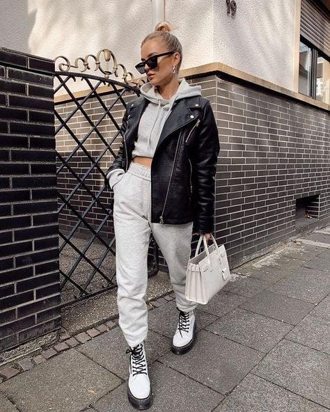 Chica usando unos jogger, sudadera y chaqueta de cuero en conjunto con unas botas Dr. Martens de color blanco mientras está caminando por la calle