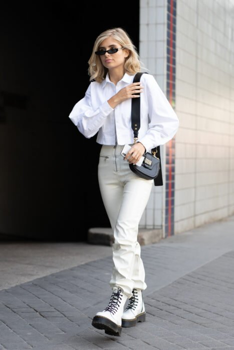Girl wearing a totally white look with white Dr. Martens accompanied by a black bag