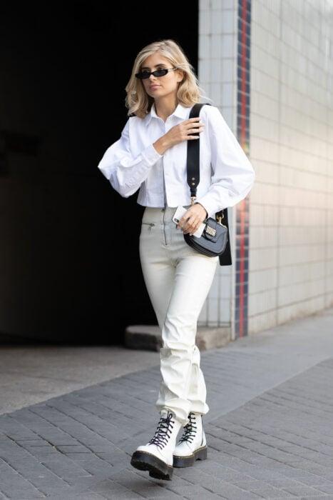 Chica usando un look totalmente blanco con unas Dr. Martens de color blanco acompañado de un bolso de color negro