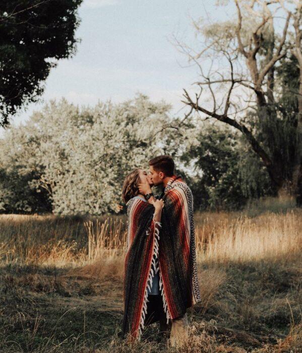 Pareja besándose en el bosque