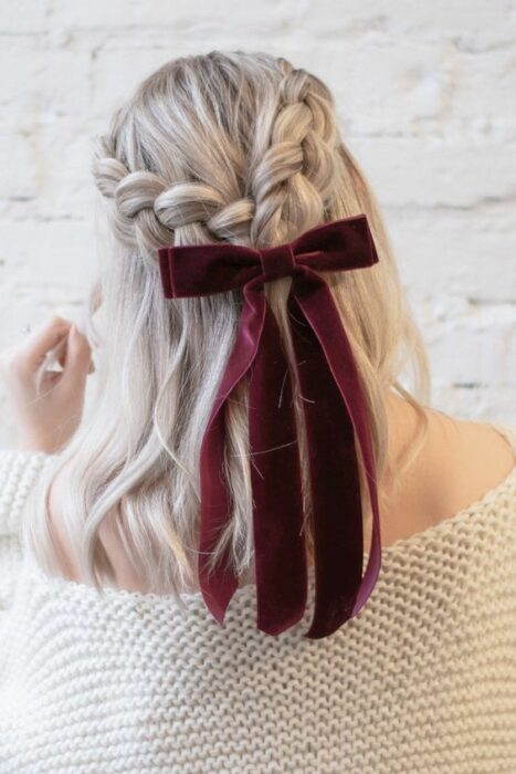 Girl with two braids decorated with cherry colored bow