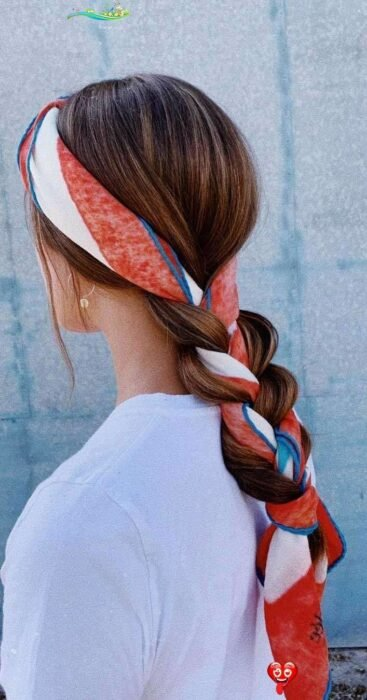 Girl with hair tied in a braid and decorated with a scarf