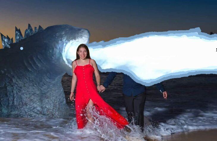 Edición de Godzila en la foto de una pareja que camina por la playa