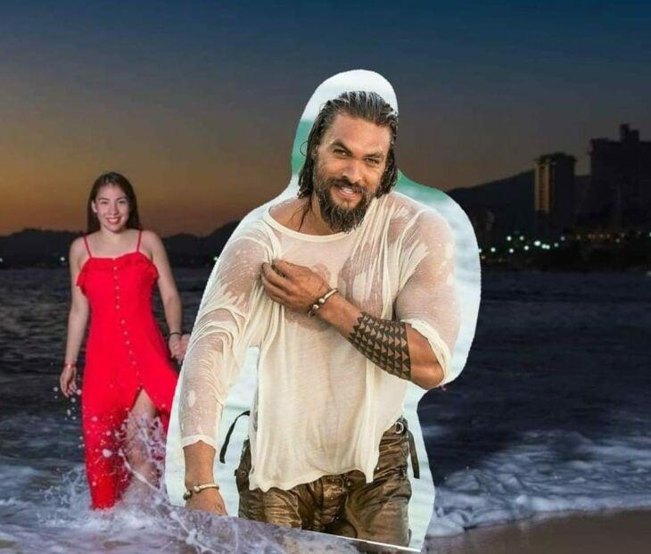 Edición de Jason Momoa en la foto de una pareja que camina por la playa