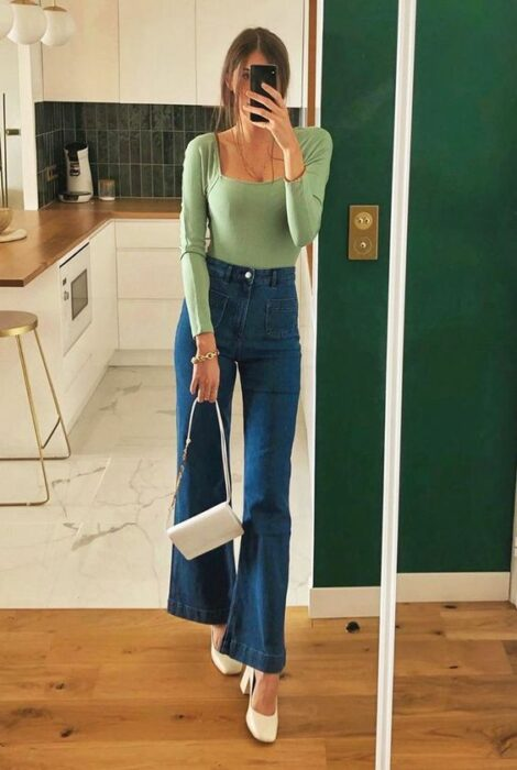 Chica usando tacones con jeans acampanados y blusa de color verde