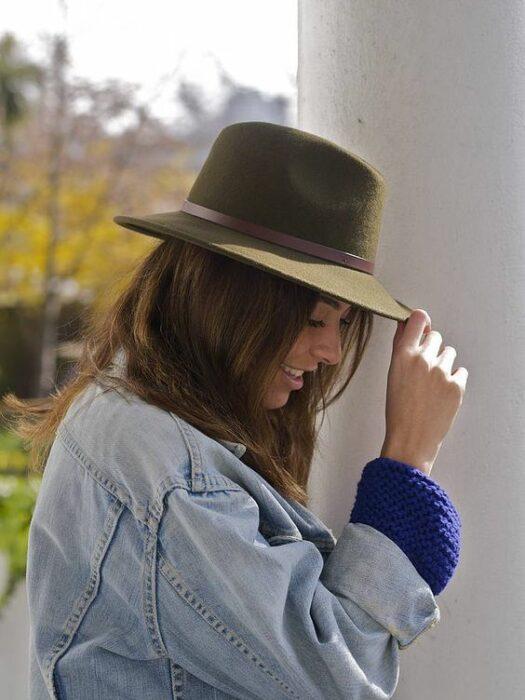 Chica usando chaqueta de mezclilla y sombrero boho color verde
