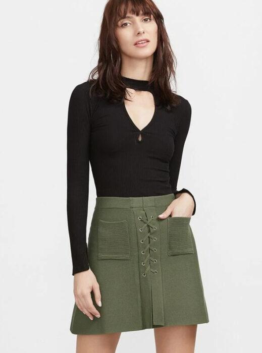 Chica usando blusa negra y mini falda color verde