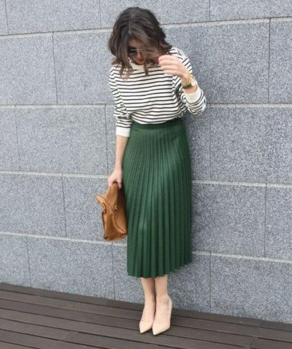 Chica usando tacones, blusa de rayas blanco y negro y maxi falda color verde