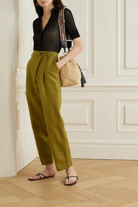 Chica usando blusa negra, pantalones verdes y zapatos nude