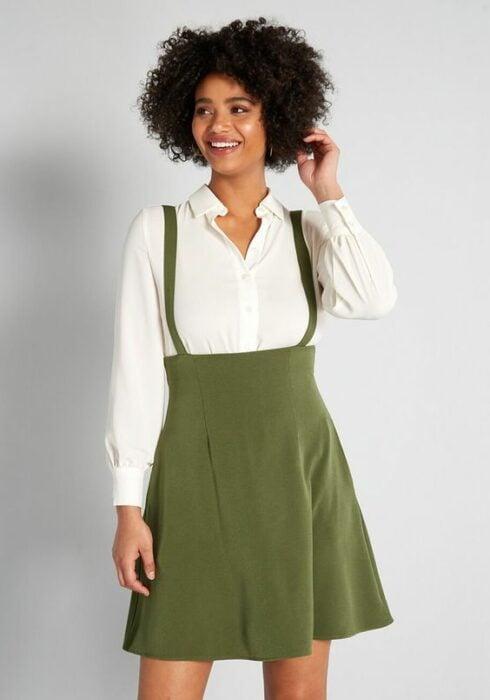 Chica de cabello rizado, usando camisa blanca con jumper color verde