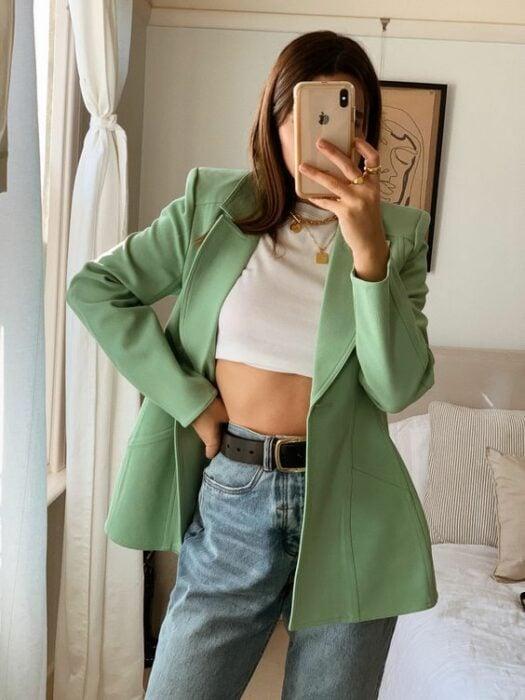 Chica usando jeans, crop top blanco y blazer color verde
