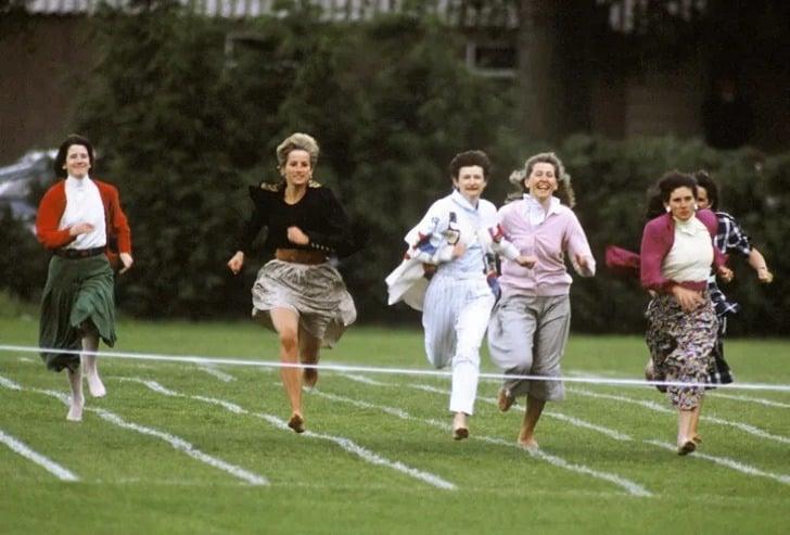 Lady Di usando una falda de color café con un saco negro y descalza corriendo junto a otras madres en un evento escolar