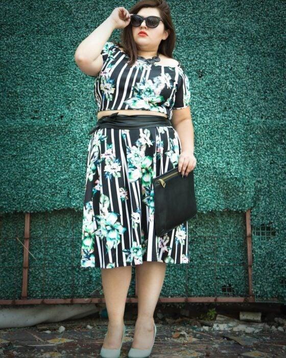 Priscila Arias la Fatshionista posando para una foto mientras usa un vestido de color verde con estampado en blanco y un clutch negro