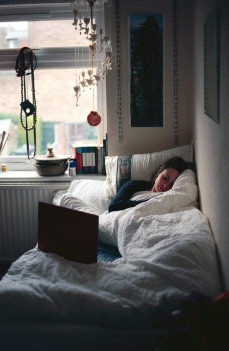 Chica recostada en la cama mirando la computadora