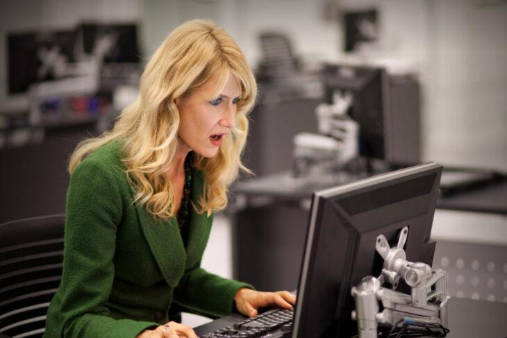 Mujer en una oficina viendo series en su computadora