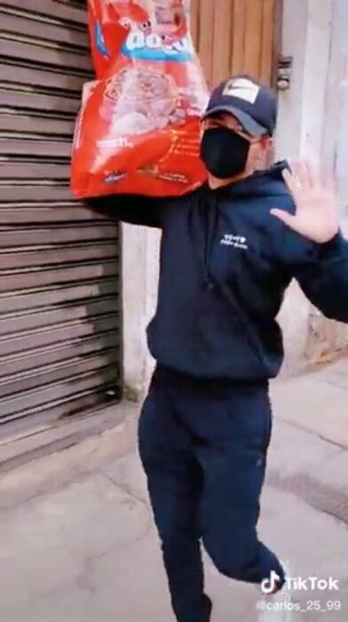 Chico cargando un bulto de croquetas para alimentar a los perritos callejeros