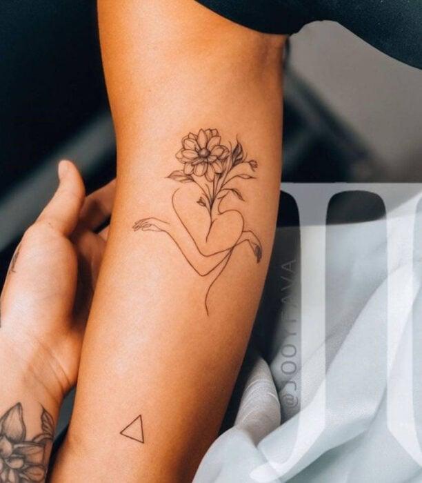 Tatuaje de la silueta de una chica abrazándose y floreciendo sobre la parte interna del brazo